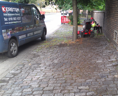 A Kersten pedestrian sweeper removing moss from block paving